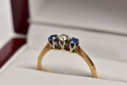A YELLOW METAL THREE STONE RING, designed with a central, claw set old cut diamond, flanked with