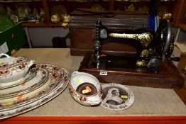 A MECHANICAL SINGER SEWING MACHINE WITH WOODEN CASE, together with a graduated set of platters,