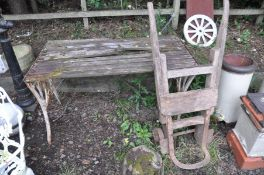A GARDEN TABLE in need of restoration with a slatted wood top and cast iron ends width 123cm depth