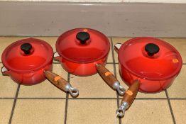 A GRADUATED SET OF THREE LE CREUSET RED ENAMEL SAUCEPANS AND LIDS, wooden handles, diameters 16cm,