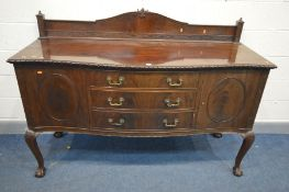AN EDWARDIAN MAHOGANY SERPENTINE SIDEBOARD with a raised back with blind fretwork detail, on a