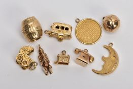 NINE 9CT GOLD CHARMS, to include a barrel, a hinged caravan, a pram and a telephone, all with 9ct