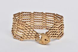 A 9CT GOLD WIDE GATE BRACELET, the gate bracelet with graduated terminals to the heart padlock clasp