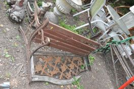 A DISTRESSED CAST IRON GARDEN BENCH with pierced metal back panel and wooden slatted seat 122cm