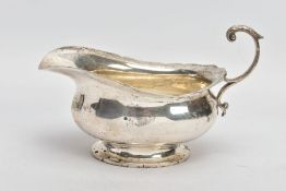 A GEORGE V SILVER SAUCE BOAT, plain polished body, wavy detailed rim, scroll and leaf detailed