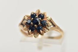 A 9CT GOLD SAPPHIRE CLUSTER DRESS RING, of a flower shape, set with seven circular cut blue