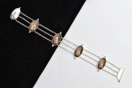 A SILVER SMOKEY QUARTZ BRACELET, designed with four oval links set with smoky quartz cabochons,