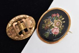 TWO VICTORIAN BROOCHES, to include a yellow metal hollow oval brooch with a foliate engraved belt