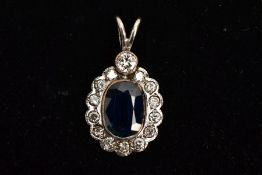 AN 18CT WHITE GOLD SAPPHIRE AND DIAMOND PENDANT, the central oval sapphire in a collet mount