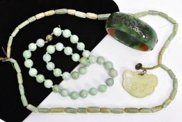 FOUR ITEMS OF JADE JEWELLERY, to include a dyed carved bangle, inner diameter 65mm, a spherical bead
