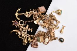 A 9CT GOLD CHARM BRACELET, a figero link chain bracelet together with various assorted charms, to