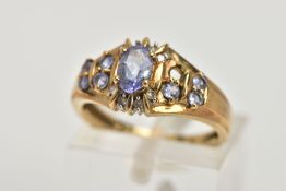 A 9CT GOLD TANZANITE AND DIAMOND DRESS RING, designed with a central claw set, oval cut tanzanite,