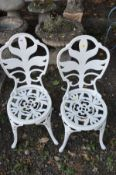 A PAIR OF MODERN WHITE PAINTED CAST IRON GARDEN CHAIRS, with pierced decoration