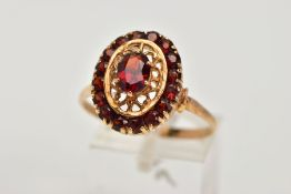 A YELLOW METAL GARNET CLUSTER RING, of an oval from, designed with a central claw set, oval cut
