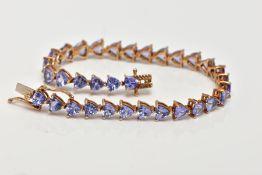A 9CT GOLD TANZANITE LINE BRACELET, designed with thirty-three claw set, triangular cut tanzanite's,