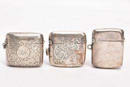 THREE SILVER VESTAS, to include two with engraved foliate designs, engraved monograms, fitted with