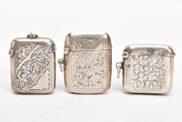 THREE EARLY 20TH CENTURY SILVER VESTAS, each with an engraved foliate design, one with engraved