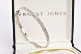 A 9CT WHITE GOLD HINGED BANGLE, the front half set with two rows of single cut diamonds, to the push