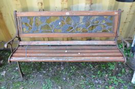 A WOODEN SLATTED GARDEN BENCH with cast metal ends and a floral back, width 123cm x depth 54cm x