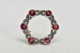 A WHITE METAL GARNET AND MARCASITE BROOCH, of an openwork circular form, set with six circular cur