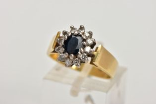 AN 18CT GOLD DIAMOND AND SAPPHIRE CLUSTER RING, centring on an oval cut deep blue sapphire, within a