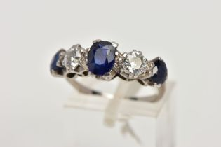 A WHITE METAL DIAMOND AND SAPPHIRE FIVE STONE RING, designed with three four claw set, oval cut blue