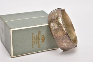 A WIDE SILVER HINGED BANGLE, half of the bangle engraved with a floral and foliate design, push