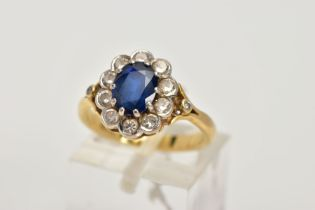 AN 18CT GOLD SAPPHIRE AND DIAMOND CLUSTER RING, centring on an oval cut blue sapphire, within a