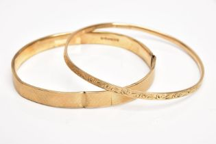 A 9CT GOLD BANGLE AND A YELLOW METAL BANGLE, the first an AF bangle of an engine turned design, (