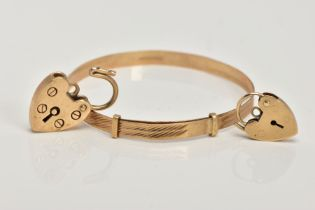 A 9CT GOLD CHILDS BANGLE AND TWO HEART SHAPED CLASPS, the child's bangle with a textured design,