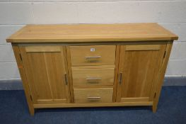 A SOLID OAK SIDEBOARD with two doors flanking three drawers, width 137cm x depth 47cm x 85cm (