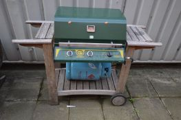 AN 'THE AUSTRALIAN BARBECUE' COMPANY TRIPLE BURNER BBQ set on a wooden slatted trolley, with 13kg