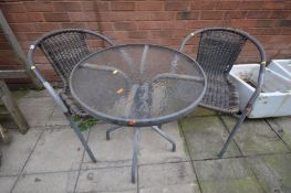 A CIRCULAR METAL FRAMED GARDEN TABLE, with a glass top, diameter 61cm together with two matching