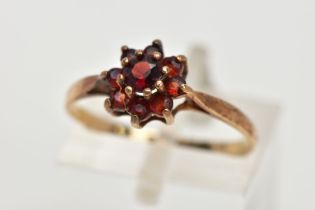A 9CT GOLD GARNET CLUSTER RING, set with circular cut garnets, tapered shoulders, hallmarked 9ct