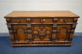 A REPRODUCTION SOLID OAK SIDEBOARD, with three drawers above two arched panelled doors flanking a