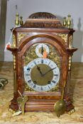 AN EARLY 20TH CENTURY WALNUT AND GILT METAL QUARTER STRIKING BRACKET CLOCK, the carved dome