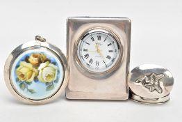 A SILVER ENAMEL COMPACT, A SILVER BEDSIDE CLOCK AND A SILVER PILL BOX, the compact of a circular