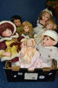 A BOX OF COLLECTORS DOLLS, to include seven dolls, a heavy porcelain soft bodied baby doll marked