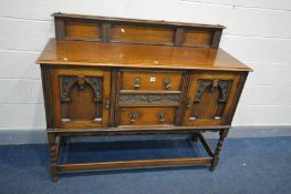 AN EDWARDIAN OAK SIDEBOARD with a raised back, two doors flanking two drawers with brass handles,