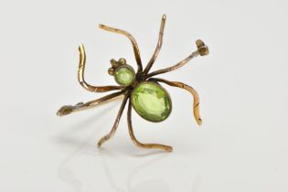 A YELLOW METAL SPIDER BROOCH, set with an oval and a circular cut peridot to the body and head, each
