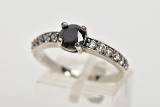 A WHITE METAL CUBIC ZIRCONIA DRESS RING, designed with a central circular cut black stone assessed
