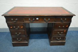 A MAHOGANY PEDESTAL DESK, with oxblood and gilt tooled leather inlayed top and seven assorted