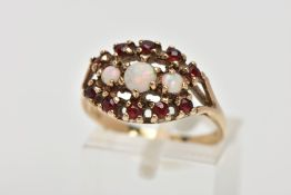 A 9CT GOLD OPAL AND GARNET CLUSTER RING, the cluster of an oval shape, set with three graduated