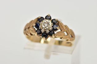 A 9CT GOLD SAPPHIRE AND DIAMOND CLUSTER RING, designed with a star set, single cut diamond, within a