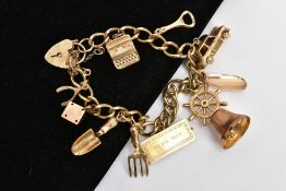 A 9CT GOLD CHARM BRACELET, suspending nine charms in forms such as a bell, car, bottle opener, dice,
