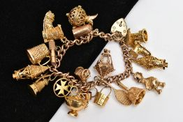 A HEAVY YELLOW METAL CHARM BRACELET, suspending nineteen charms in forms such as a wishing well,