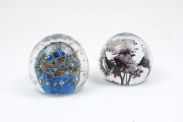 Two paperweights of modern design, the former with blue and orange centrepiece and glass bubbles,