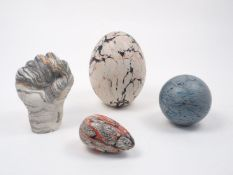 A group of four marbled effect wood turned objects, to include a raised clenched fist, 20cm high,
