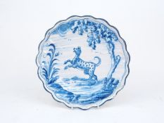 A Dutch Delft cabinet plate, late 19th/early 20th century, possibly 'Die Drie Klokken', of scalloped
