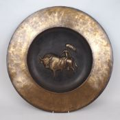 A large modern brass charger, 20th Century, with central decorative scene of a nude female riding